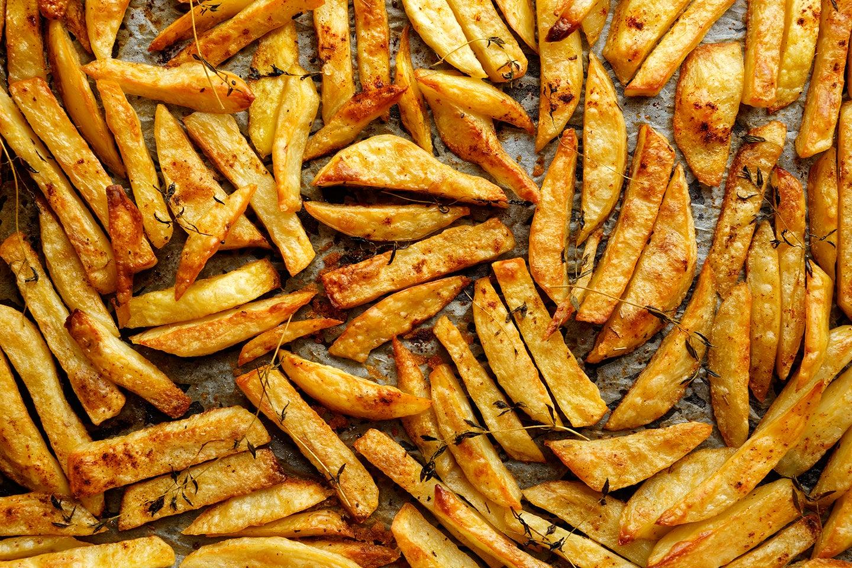 Seasoned fries on a baking sheet.