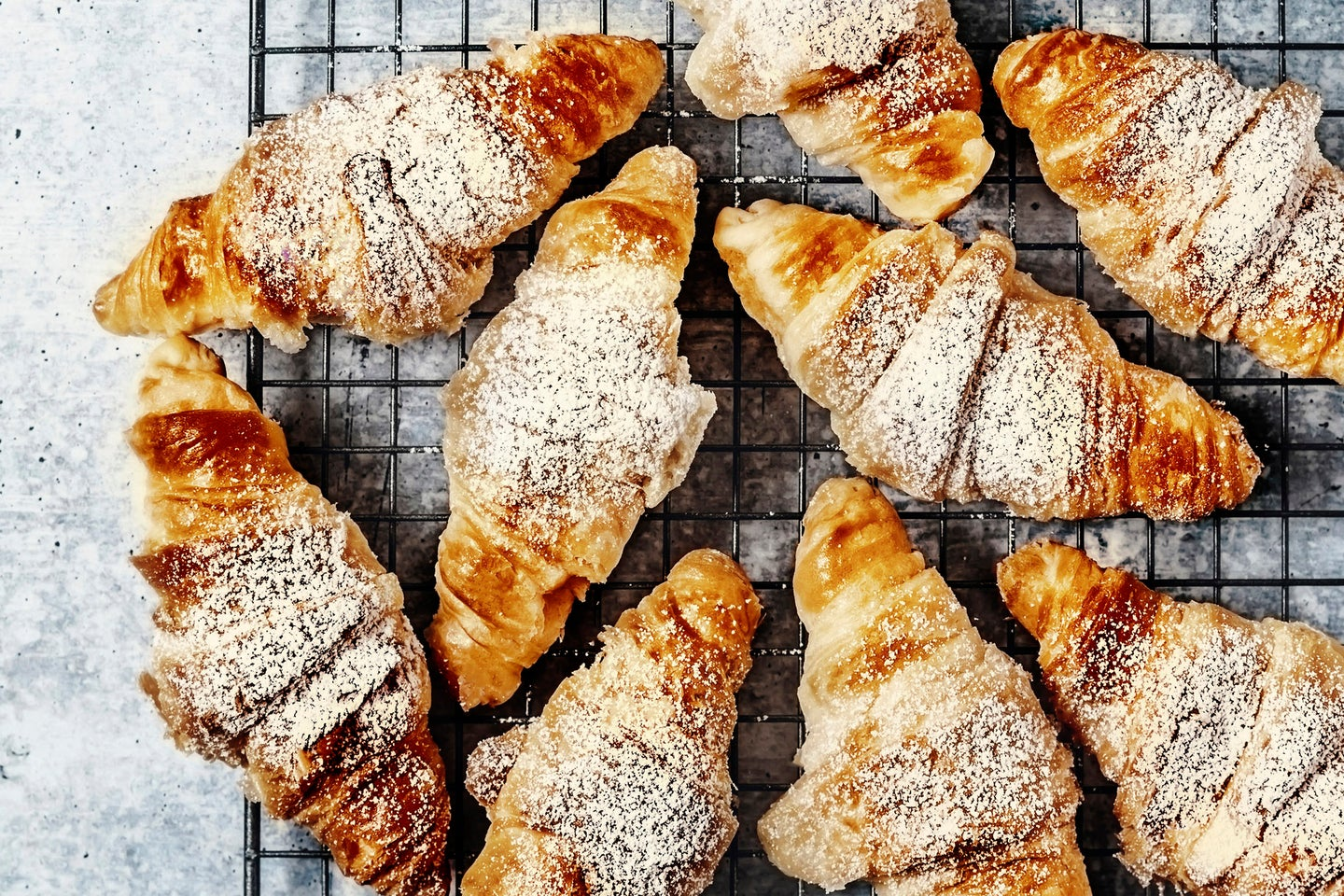 Croissants on a cooling rack on gray background