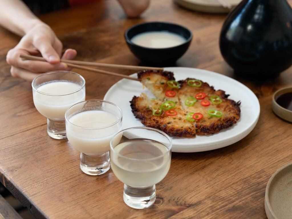 Drinking makgeolli and eating korean pancake