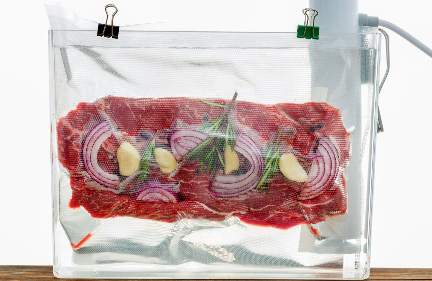 Sous vide bag containing raw beef, onions, and herbs